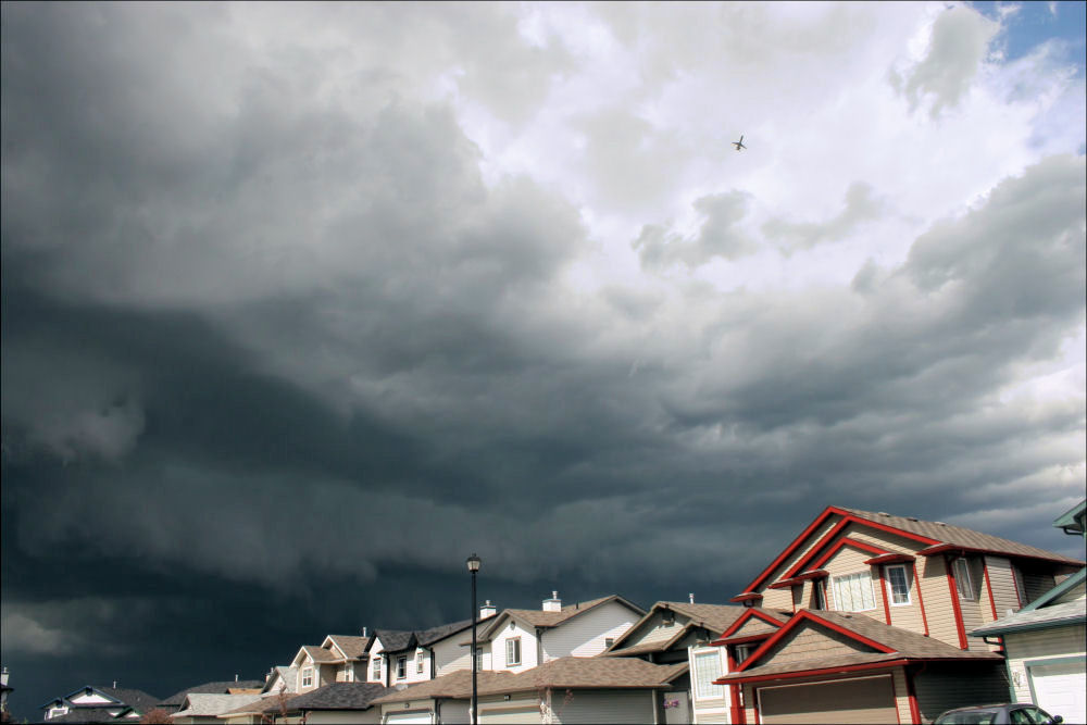Storm cell and plane, upper right, Airdrie, Alberta