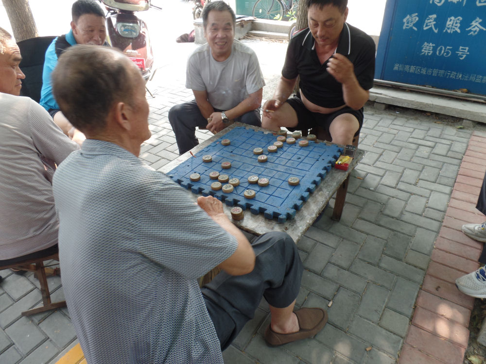 Men playing checkers as they do evry afternoon and evening in Zibo, China