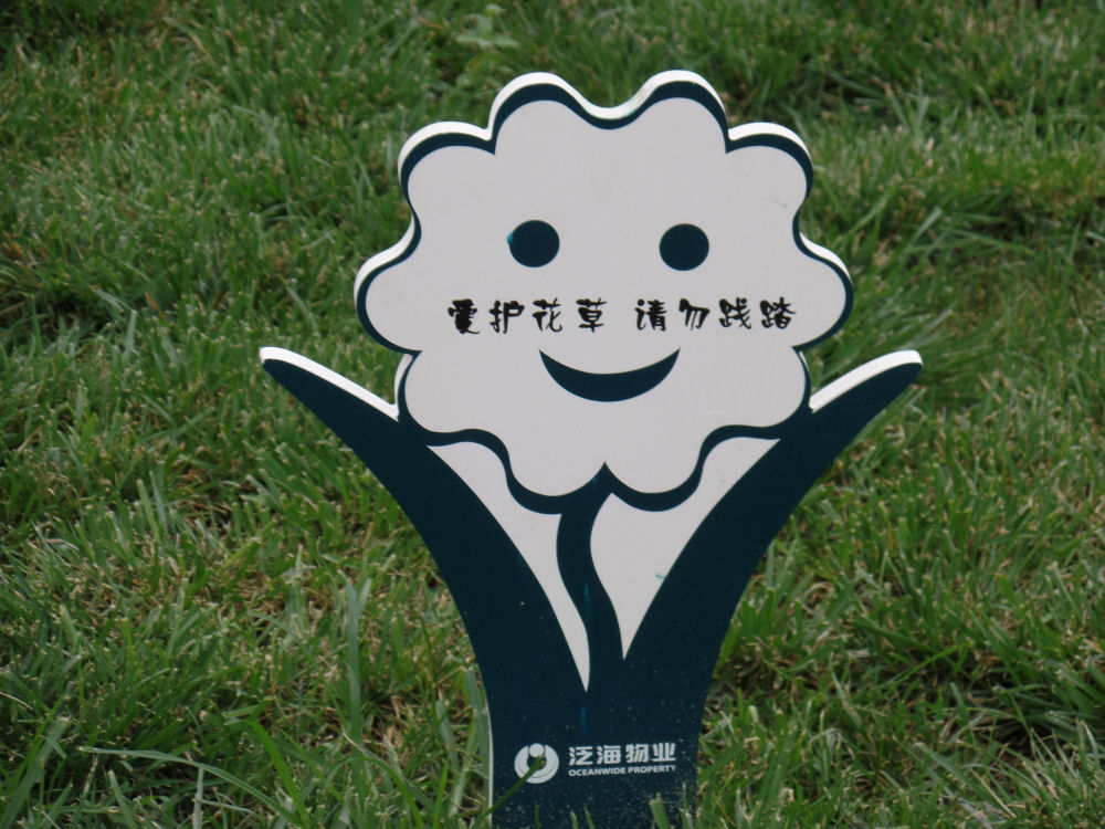 Sign on a small patch of grass in a city park, Bejing, China