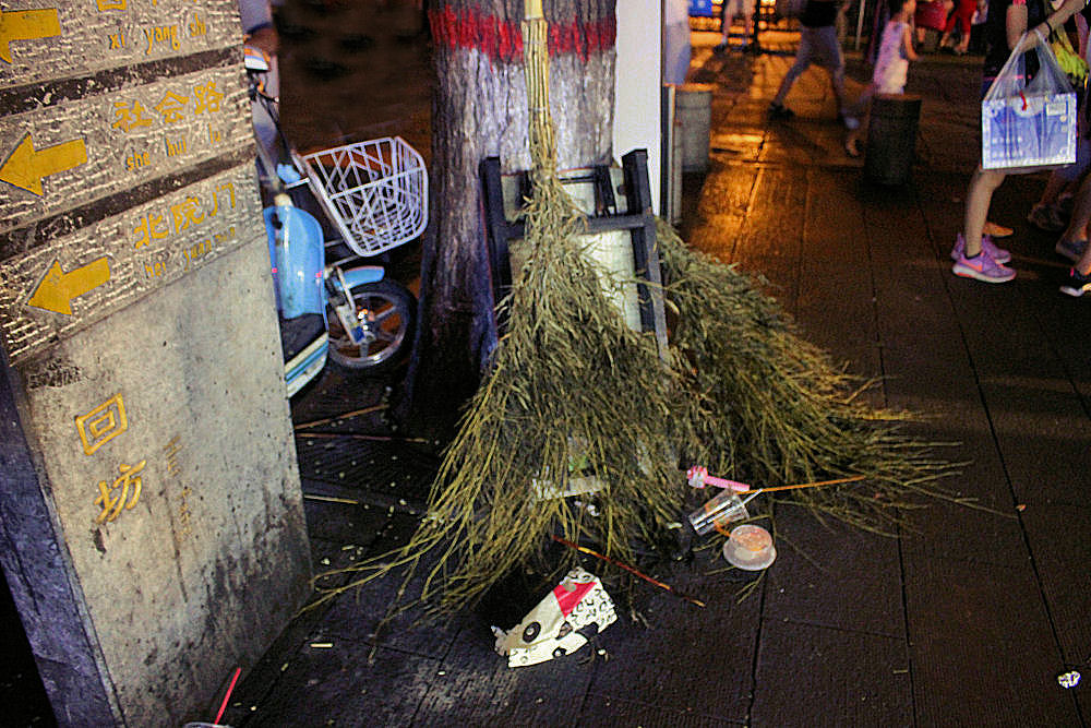 Night market in Xi'an, China - street sweeper's brooms are branches